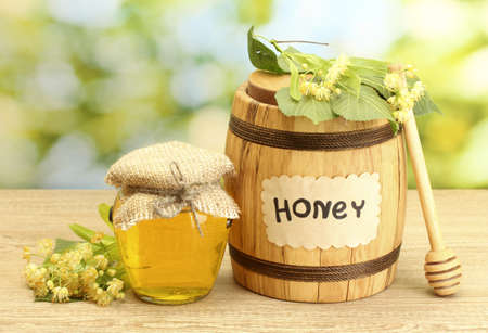 jar and barrel with linden honey and flowers on wooden table on green background Stock Photo - 14836099