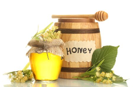 jar and barrel with linden honey and flowers isolated on white photo
