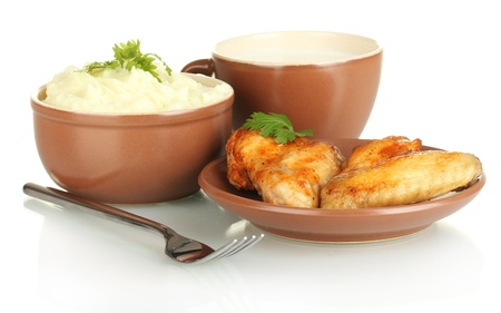Mashed potato with parsley in the bowl and roasted chicken wings in the plate and cup with milk isolated on white photo