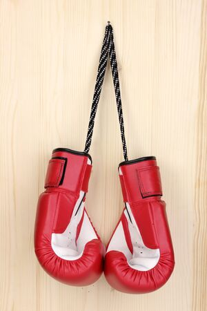 Red boxing gloves hanging on wooden background photo