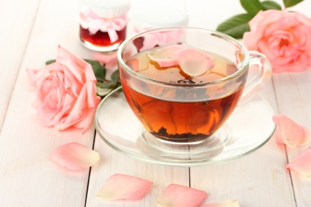 cup of tea with roses and jam on white wooden table photo