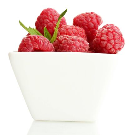ripe raspberries with mint in bowl isolated on white photo