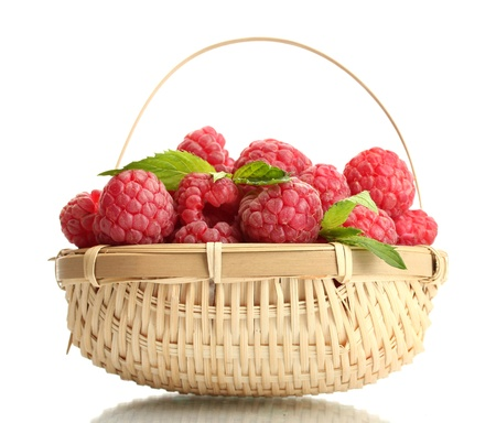 ripe raspberries in basket with mint  isolated on white photo