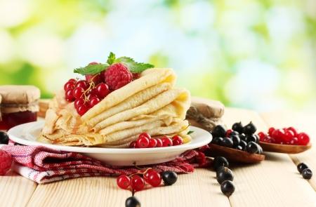 hot cakes: panqueques con bayas, mermelada y miel en la mesa de madera sobre fondo verde Foto de archivo