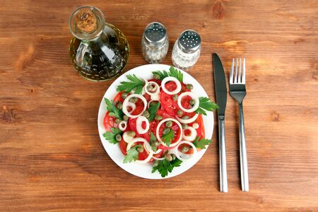Salad with capers in the plate on wooden background photo