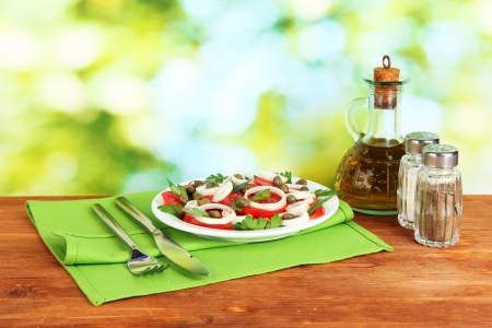 Salad with capers in the plate on bright green background photo