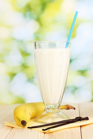 Banana milk shake on wooden table on bright background photo