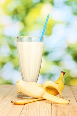 Banana milk shake on wooden table on bright background photo
