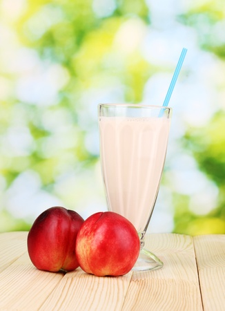 Peach milk shake on wooden table on bright background photo