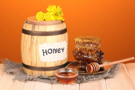 Barrel of honey and honeycomb on wooden table on orange background photo