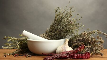 desiccated: dried herbs in mortar and vegetables, on wooden table on grey background