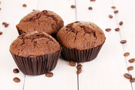 Fresh muffins on wooden background photo