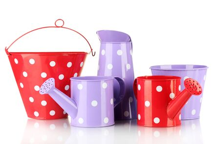 Purple and red watering cans and buckets with white polka-dot isolated on white photo