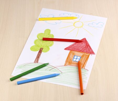 Children's drawing of house and pencils on wooden background photo