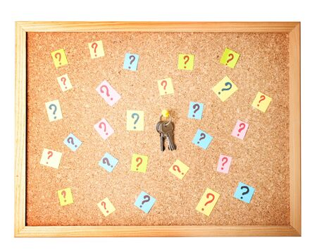 Keys with many question marks on cork board photo