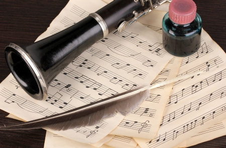 Musical notes and clarinet on wooden table Stock Photo