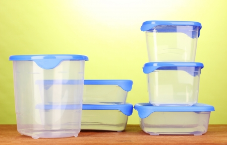 tupperware: Plastic containers for food on wooden table on green background Stock Photo