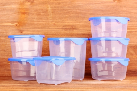 tupperware: Plastic containers for food on wooden background Stock Photo