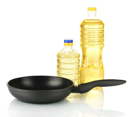Pan with bottle of oil isolated on white photo
