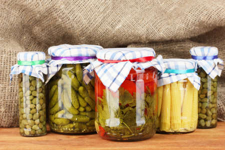 Banks canned vegetables on sack background photo