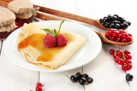Delicious pancake with berries and honey on plate on wooden table photo