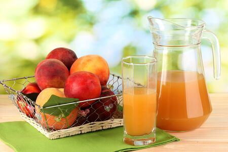 Ripe peaches and juice on wooden table on natural background photo