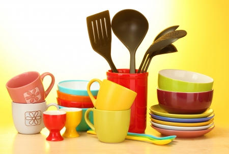 bright empty bowls, cups and kitchen utensils on wooden table on yellow background photo