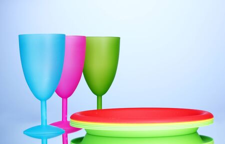 Bright plastic tableware on blue background photo