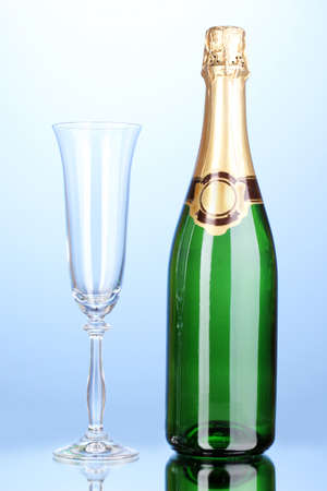 gold capped: Bottle of champagne and goblet on blue background Stock Photo