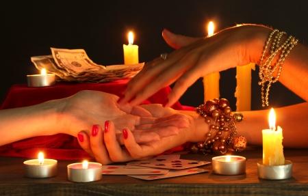 psychic: la lectura de la mano las líneas en manos de una mujer en negro backcground