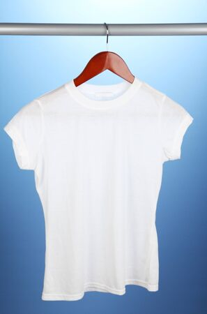 White t-shirt on hanger on blue background photo