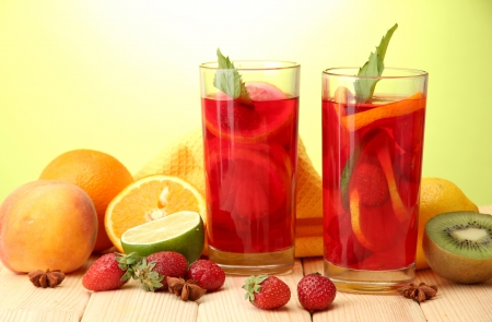 Refreshing sangria in glasses with fruits, on wooden table, on green background photo