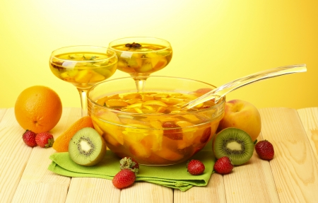 punch in bowl and glasses with fruits, on wooden table, on yellow background photo