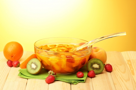 punch in glass bowl with fruits, on wooden table, on yellow background photo