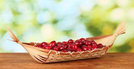 fresh cornel berries in wicker basket on green background close-up photo