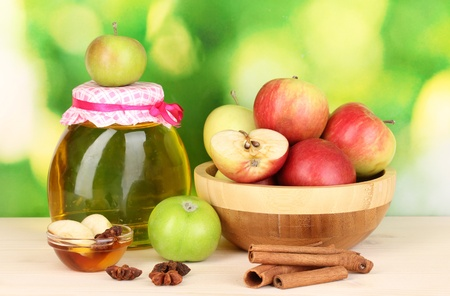 Honey and apples with cinnamon on wooden table on natural background photo