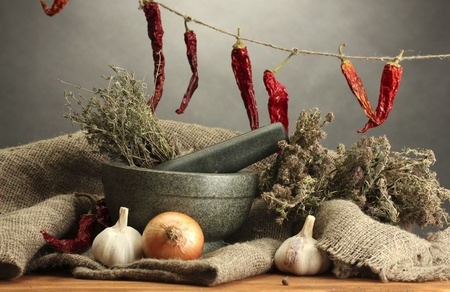 dried herbs in mortar and  vegetables, on wooden table on grey background photo