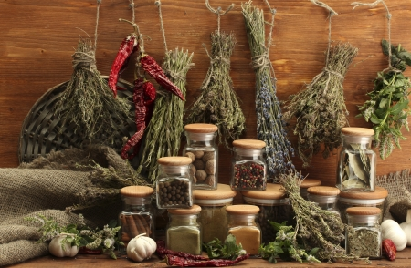 dried herbs, spices and and pepper, on wooden background photo