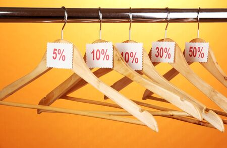 wooden clothes hangers as sale symbol on orange background  Stock Photo - 14921655
