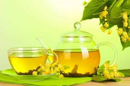 teapot and cup with linden tea and flowers on wooden table on green background  photo