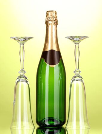 Bottle of champagne and goblets on green background photo