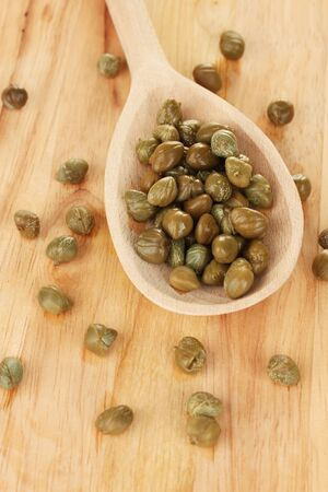 green capers in wooden spoon on wooden background close-up photo