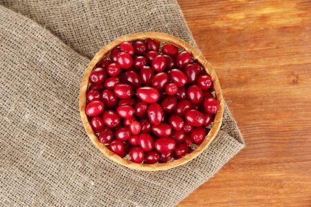 fresh cornel berries in wicker basket on wooden background close-up photo