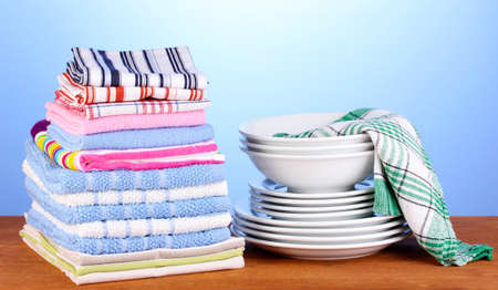 kitchen towels with dishes on blue background close-up photo