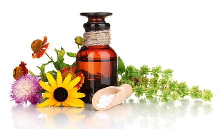 homeopathic: medicine bottle with tablets and flowers isolated on white