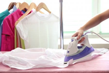 Woman hand ironing a shirt, on cloth background photo
