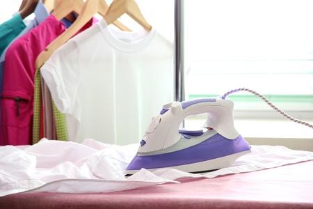 ropa colgada: Plancha el�ctrica y la camisa, en el fondo de tela Foto de archivo