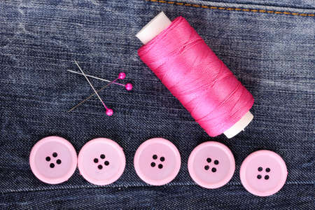 Colorful sewing buttons with thread on jeans closeup photo