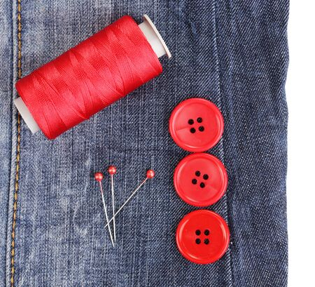 Colorful sewing buttons with thread on jeans isolated on white photo