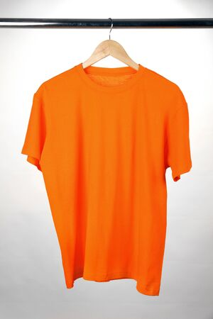 Orange t-shirt on hanger on white background photo